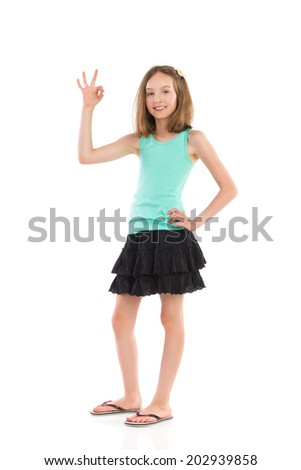 It was perfect! Young girl in teal shirt and black skirt showing ok hand sign. Full length studio shot isolated on white. - stock photo