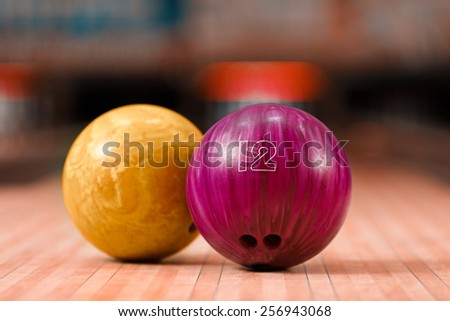 It will be strike. Closeup of two bright bowling balls staying against bowling alley - stock photo