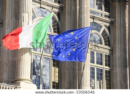 italian and Eurpean flag in wind on monument facade - stock photo