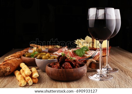 Italian antipasti wine snacks set. Cheese variety, Mediterranean olives, pickles, Prosciutto di Parma, tomatoes, artichokes and wine in glasses. Spanish tapas