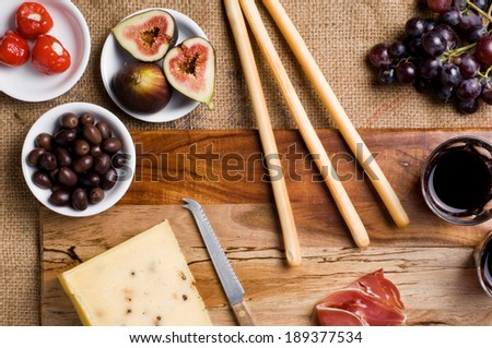 Italian Antipasto table setting with Pecorino Cheese, Wine, Figs, Grapes, Olives, Prosciutto, Stuffed Peppers, and bread sticks on chopping board. - stock photo