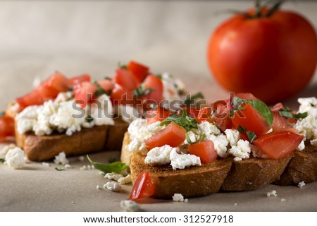 Italian Appetizer Bruschetta with roasted tomatoes, cheese and herbs - stock photo