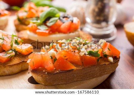 Italian Appetizer Bruschetta with roasted tomatoes, mozzarella cheese, garlic and herbs - stock photo