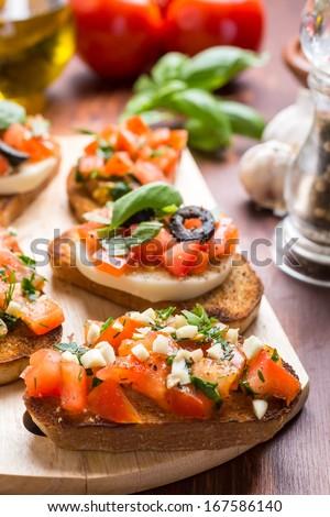 Italian Appetizer Bruschetta with roasted tomatoes, mozzarella cheese, garlic and herbs - stock photo