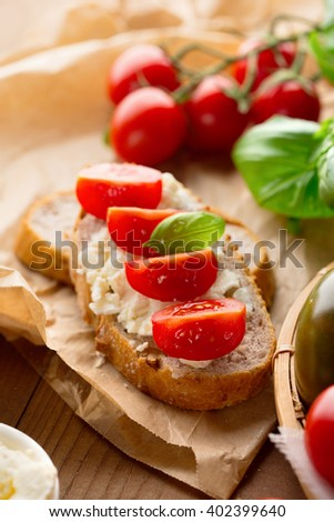 Italian appetizer - bruschetta with tomatoes, feta cheese and basil, on rustic wooden background, selective focus