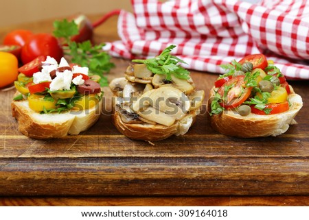 Italian appetizer bruschetta with tomatoes, olives, cheese and mushrooms - stock photo