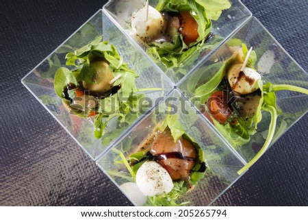 Italian appetizer with tomatoes, rocket, mozzarella and balsamic vinegar in small serving bowls - stock photo