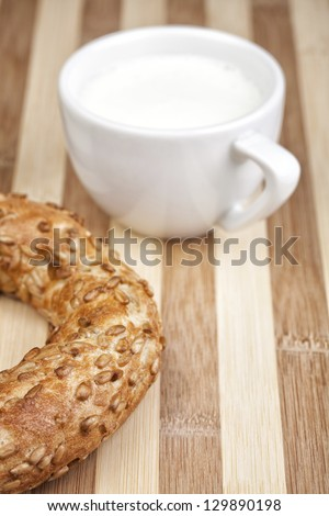 Italian bagel on wooden table with cup of fresh milk. Selective focus. - stock photo