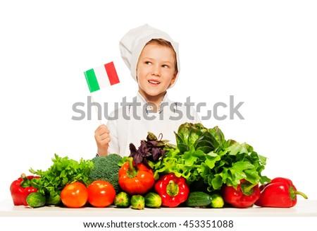 Italian boy in cook's toque preparing fresh salad - stock photo