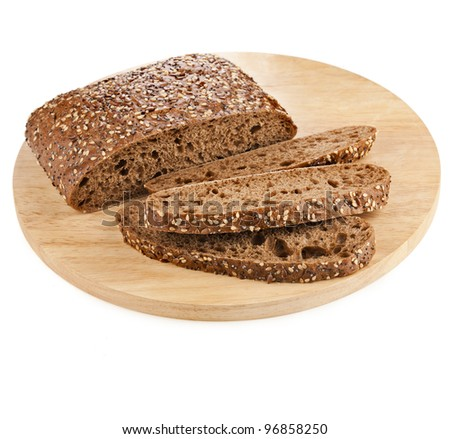 Italian bread with sesame seeds, flax on round kitchen cutting board - stock photo
