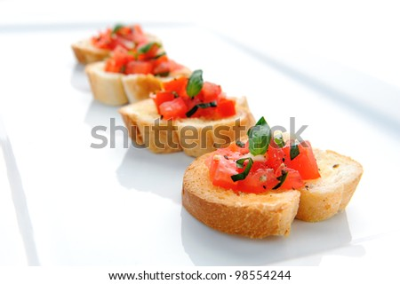 Italian brushetta; sliced baguette topped with a mixture of chopped tomato, garlic and basil - stock photo
