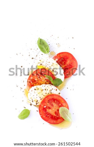 Italian caprese salad - modern artistic composition. Mozzarella cheese, tomato, basil and olive oil on white background from above. Layout with free text space. - stock photo