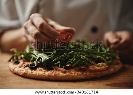 Italian chef cooking pizza on wood table in the kitchen. Close-up of fresh delicious pizza with greens and tomatoes.  - stock photo