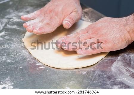 Italian chef preparing pizza dough - stock photo