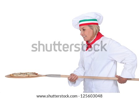 Italian chef putting a pizza in the oven - stock photo