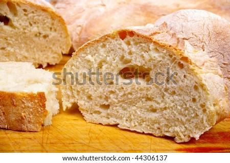 italian ciabatta slipper bread cut on wooden board - stock photo