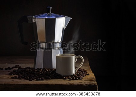 Italian coffee maker, cup of steaming coffee and whole coffee beans on an old rustic wooden table against a dark brown background with generous copy space - stock photo