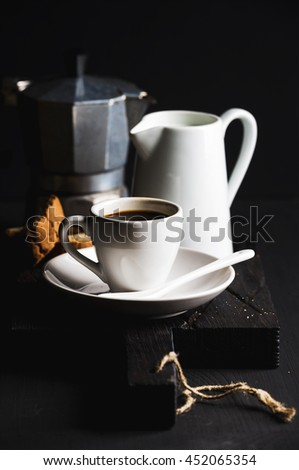 Italian coffee set for breakfast. Cup of hot espresso, creamer with milk, cantucci and moka pot on dark rustic wooden board over black background, selective focus, vertical composition - stock photo