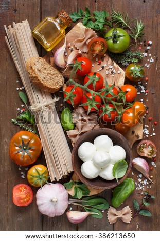Italian cooking ingredients : mozzarella, pasta, tomatoes, garlic, herbs,  olive oil and other - stock photo