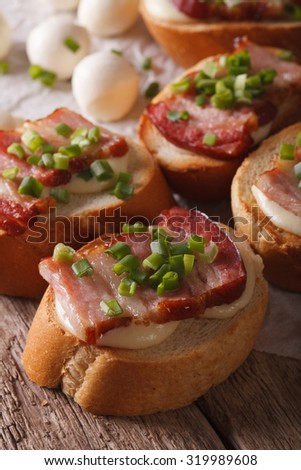 Italian crostini with bacon and mozzarella cheese close-up on the table. vertical