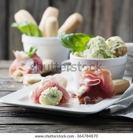 Italian crostini with cream cheese and prosciutto, selective focus and square image - stock photo