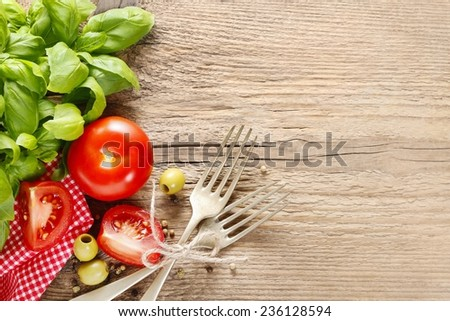 Italian cuisine background: tomatoes, olives and peppers on wooden table, copy space