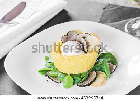 Italian cuisine- black truffle polenta basket with crispy chips and creamy sauce on white plate. Selective focus. - stock photo