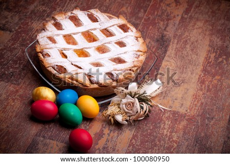 Italian Cuisine - Desserts - Neapolitan Pastiera and colorful Easter eggs. Pastiera is a wheat and ricotta pie that is also known at Naples as Pizza Gran. - stock photo