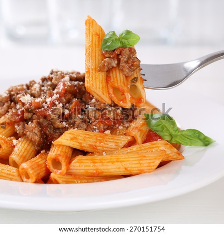 Italian cuisine eating Penne Rigatoni Bolognese sauce noodles pasta meal on a plate - stock photo