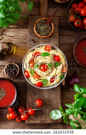 Italian cuisine. Pasta with olive oil, garlic, basil and tomatoes and tomato soup. - stock photo