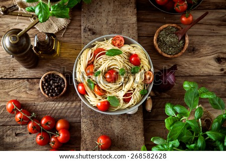 Italian cuisine. Pasta with olive oil, garlic, basil and tomatoes and tomato soup.