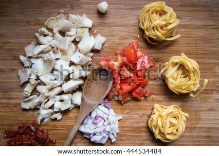 Italian cuisine. Pasta with olive oil, garlic, champignons, onion and tomatoes. Preparing tasty pasta. - stock photo