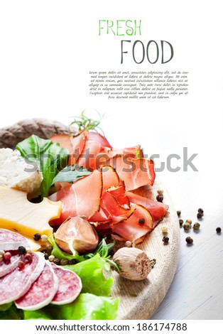 Italian cuisine. Prosciutto, cheese, salami, herbs. - stock photo