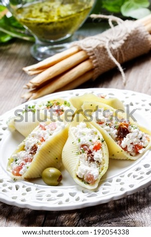 Italian cuisine: stuffed pasta shells, tomatoes and pesto sauce in the background - stock photo