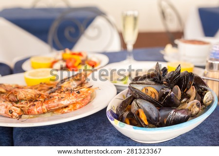 Italian cuisine. Zuppa di cozzi and grilled prawns. Shallow DOF, horizontal