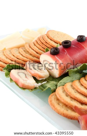 Italian delicacy consisting of prosciutto ham and mozzarella cheese roll with crackers and black olives