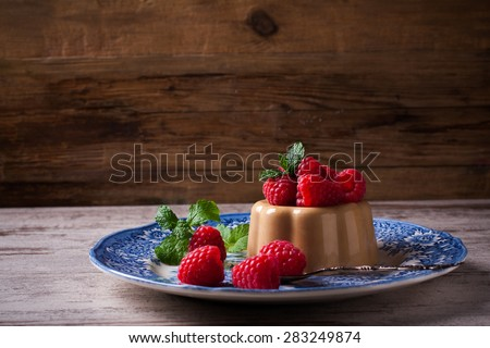 Italian dessert coffee panna cotta served on a blue plate with raspberries and fresh mint on vintage wooden background. Selective focus.  - stock photo