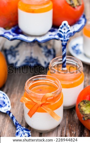 Italian dessert panna cotta in a jar with persimmon topping - stock photo