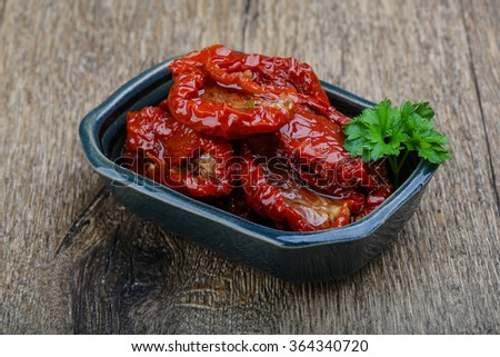 Italian Dried tomatoes with parsley on the wood background