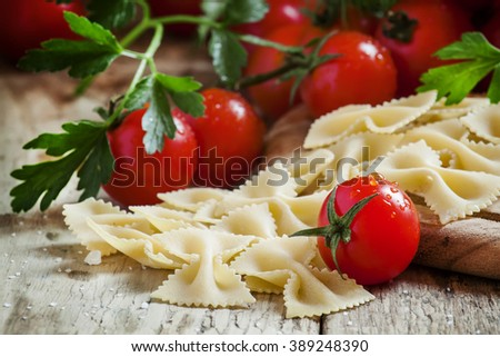 Italian dry pasta farfalle in the form of bows with cherry tomatoes and parsley on the old wooden background, selective focus