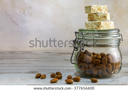 Italian festive torrone or nougat on a glass jar with almonds on bright rustic wood against a vintage wall with generous copy space in the background, selected focus, narrow depth of field - stock photo