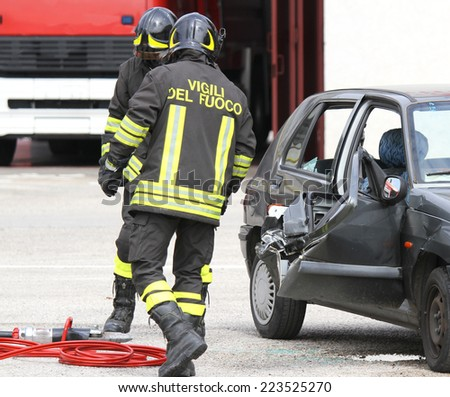 Italian firefighters and destroyed car after the accident - stock photo