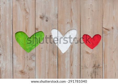 Italian flag colors carved into wooden love hearts - stock photo