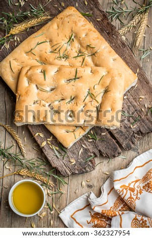 Italian focaccia bread with rosemary on wooden surface  - stock photo