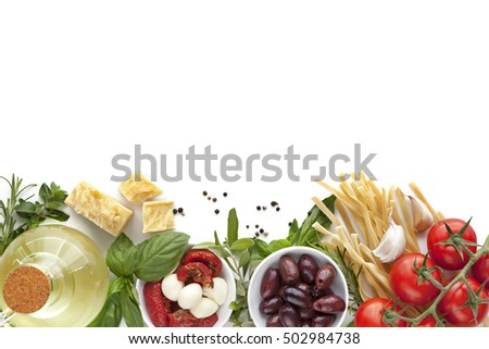 Italian food background over white.  Variety of ingredients, including olive oil, pasta, tomatoes, olives, herbs, parmesan and mozzarella.