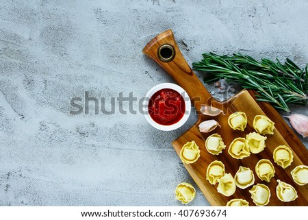 Italian food background with wooden cutting board, homemade raw tortellini, tomato sauce and rosemary over concrete textured board, place for text, border, top view. - stock photo