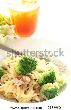 italian food, broccoli and pork spaghetti with lemon tea on white background