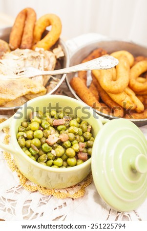Italian food ,chicken,peas and potatoes in a rustic setting.