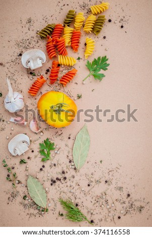 Italian food concept pasta with vegetables and spices herb rosemary ,thyme,parsley,garlic,tomato and champignon mushroom setup on brown background. - stock photo