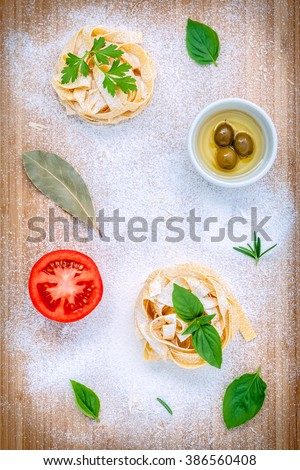 Italian food concept pasta with vegetables olive oil and spices herbs parsley , basil ,bay leaves and rosemary set up with white powder on wooden background.